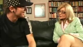 Mature blonde with glasses fucks young guy on sofa