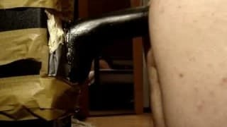A gay guy sits on a thick black dildo