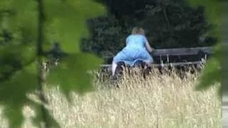 A mature couple have some fun on a bench