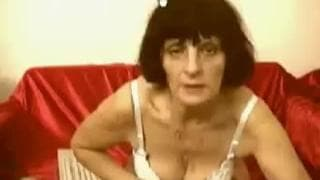 This mature woman masturbates on the couch