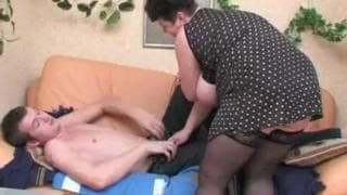 A fat cougar fucks a young guy on the couch