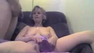 A mature woman enjoys her dildo in her chair