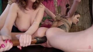 Lesbian fucks a young brunette in bondage