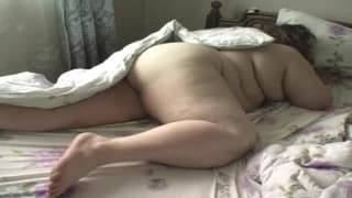 Fat woman enjoys being caresses in bed