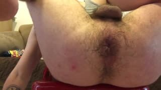 Opening his ass to sit on a long dildo